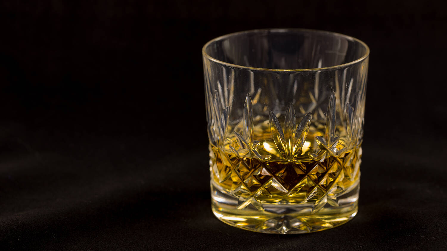 A crystal tumbler is a third full of whisky. It is displayed against a black background.