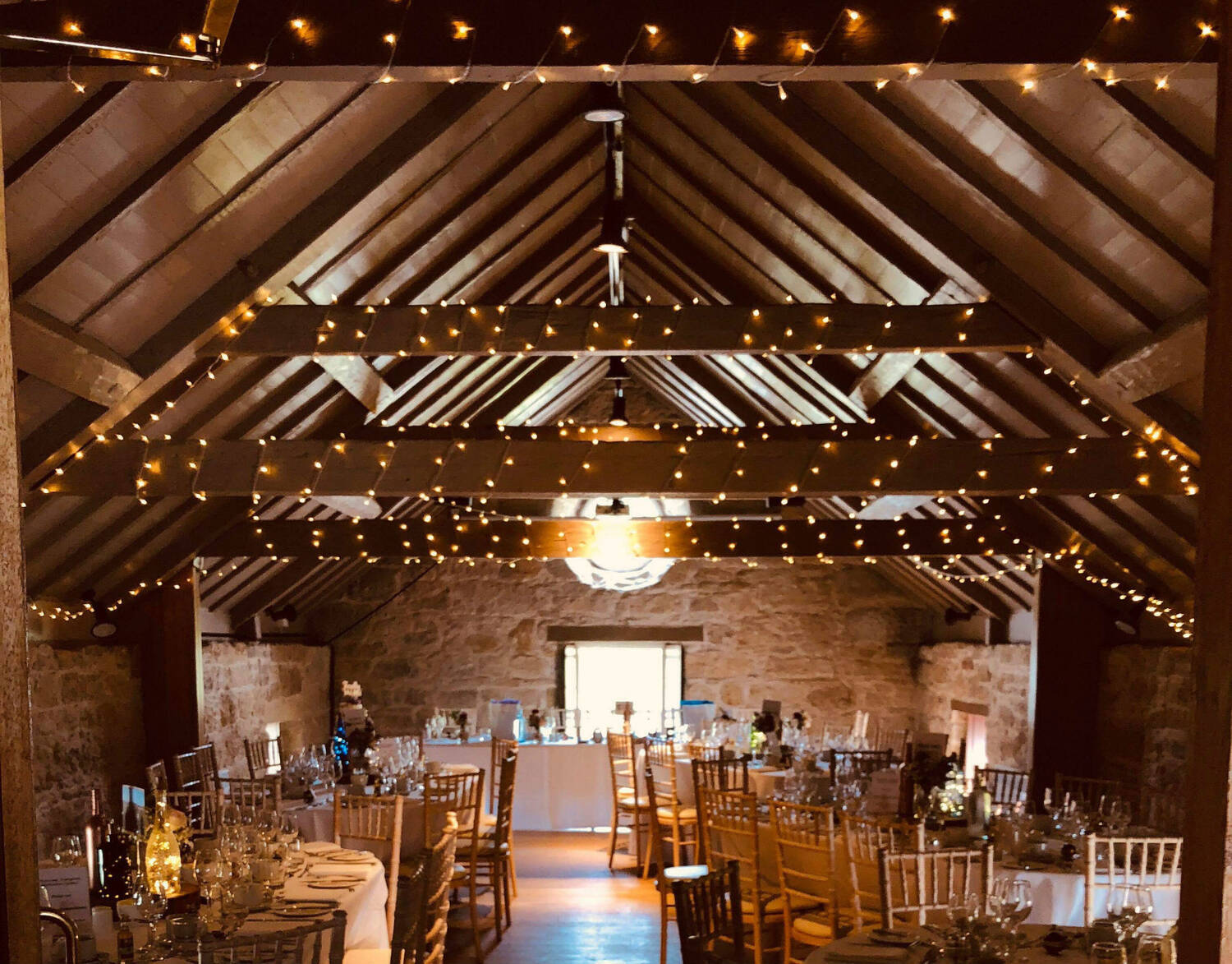 Interior of a stone barn with wooden rafters lit with fairy lights and with tables set up for a wedding reception.