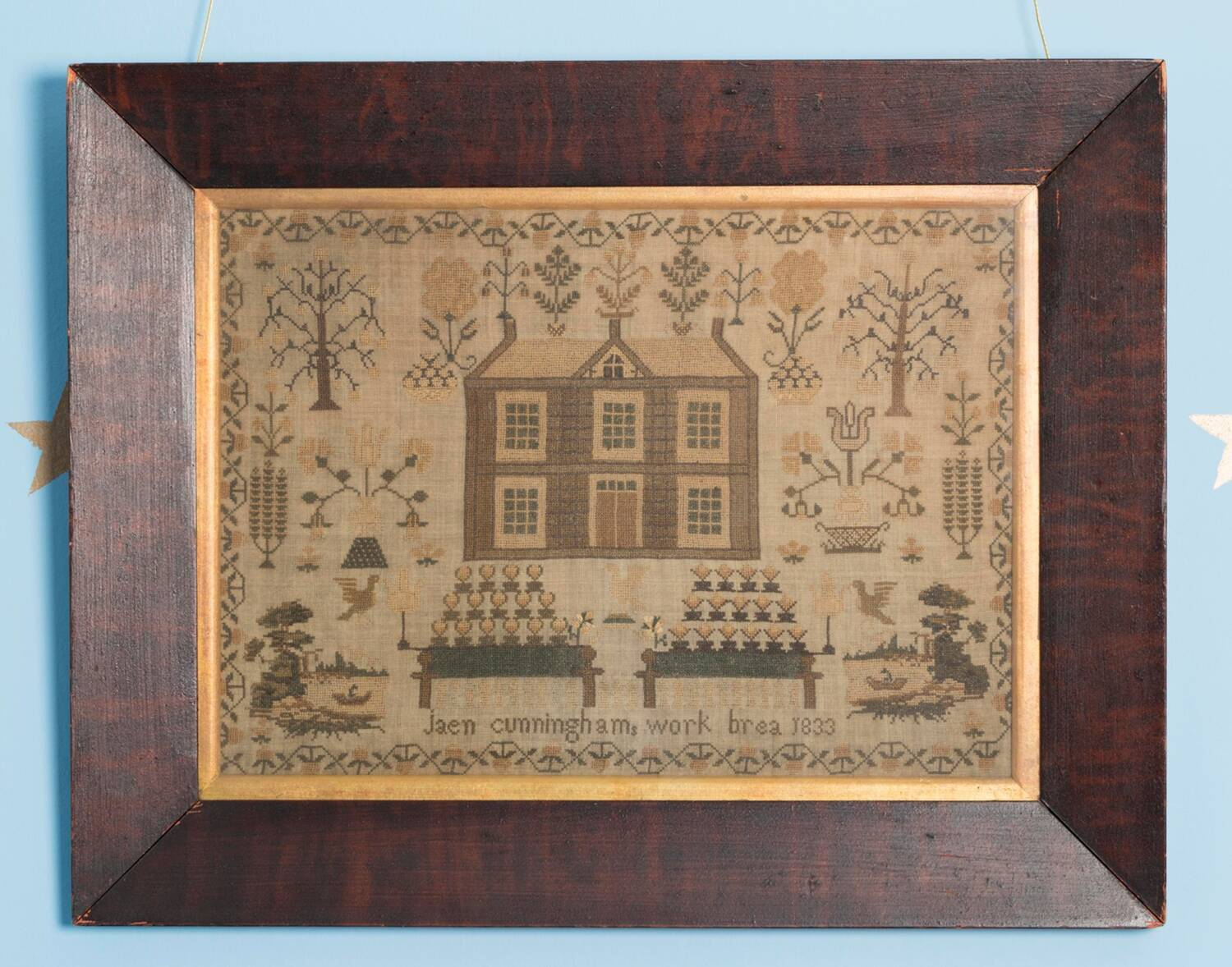 A piece of needlework on plain linen set in a dark brown frame. In the centre is a picture of a house with five windows arranged symmetrically around a centre door. The roof is pitched and has three chimneys. Around the house are small pictures of stylised trees and flowers, all sewn in coloured threads that have faded to soft greens, browns and yellow. Along the bottom are the words Jaen Cunninghams work Brea 1833. All set within a vine-like border of green stems and leaves with small yellowed flowers.