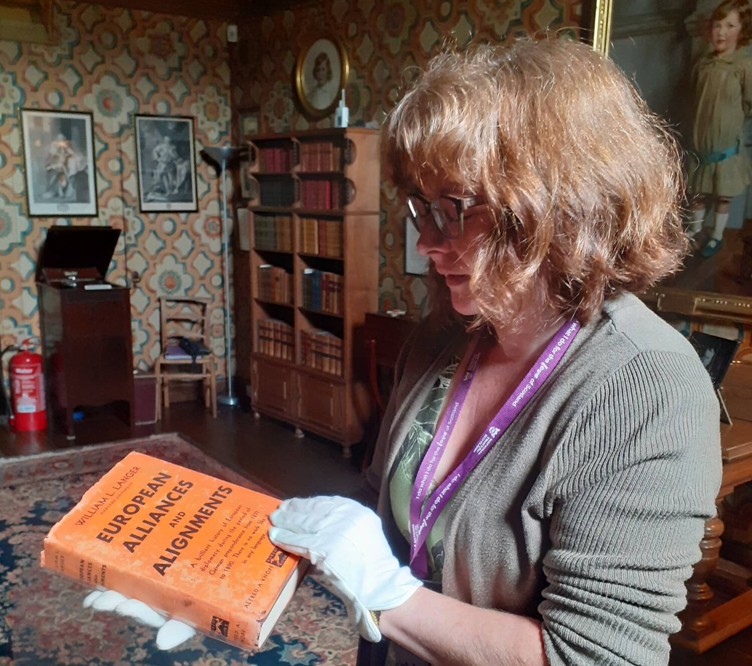 A close-up of a woman with white conservation gloves holding a hardback book with an orange cover.