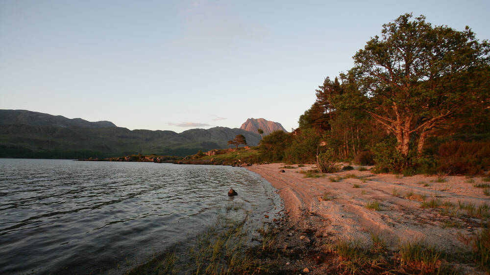 The sunset shimmers over Loch Maree, with a mountain in the background.