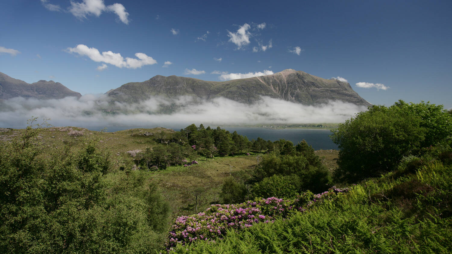 Looking across to the mountains of Torridon on a sunny, summer day. Cloud swirls around the mountain base, just above the loch.