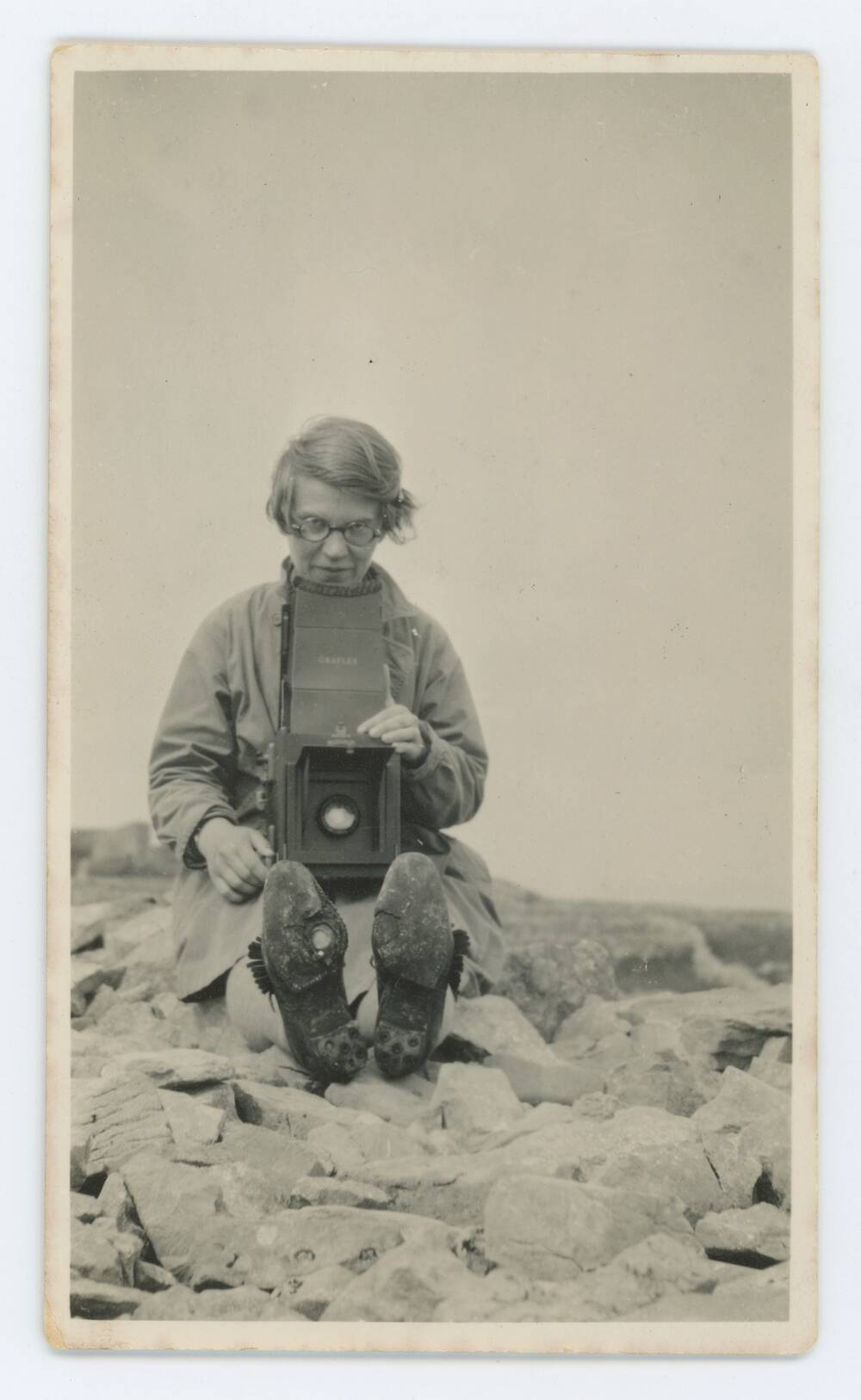 A sepia photo of a woman sitting on rocky ground. She holds a large camera and the soles of her boots face the viewer.
