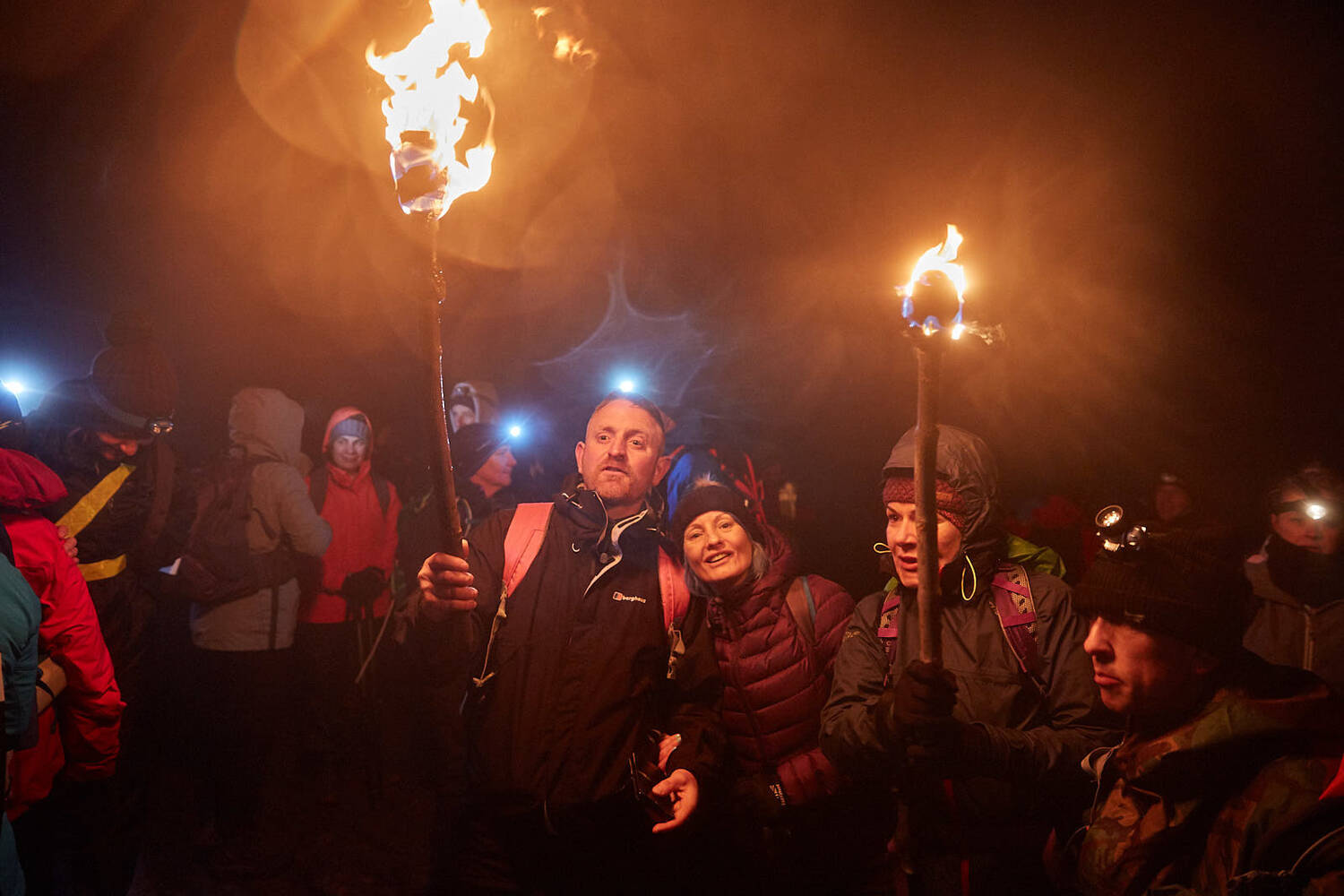 Participants in the 2019 Torchlight Challenge hold their flaming torches aloft