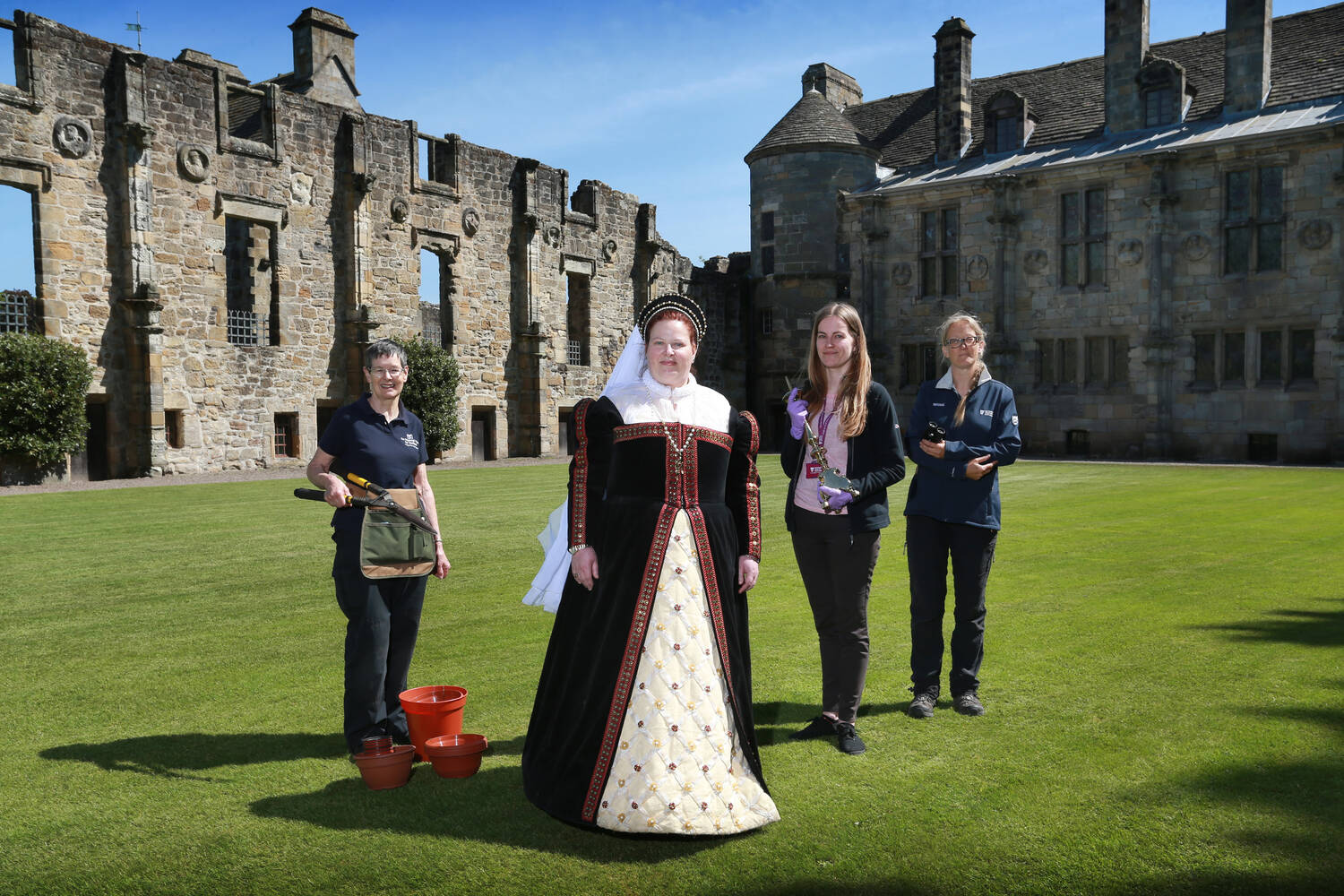 Volunteers stand on the lawn at Falkland Palace. One is dressed as Mary, Queen of Scots; the second holds a gardening tool; the third a candlestick; and the fourth a pair of binoculars.