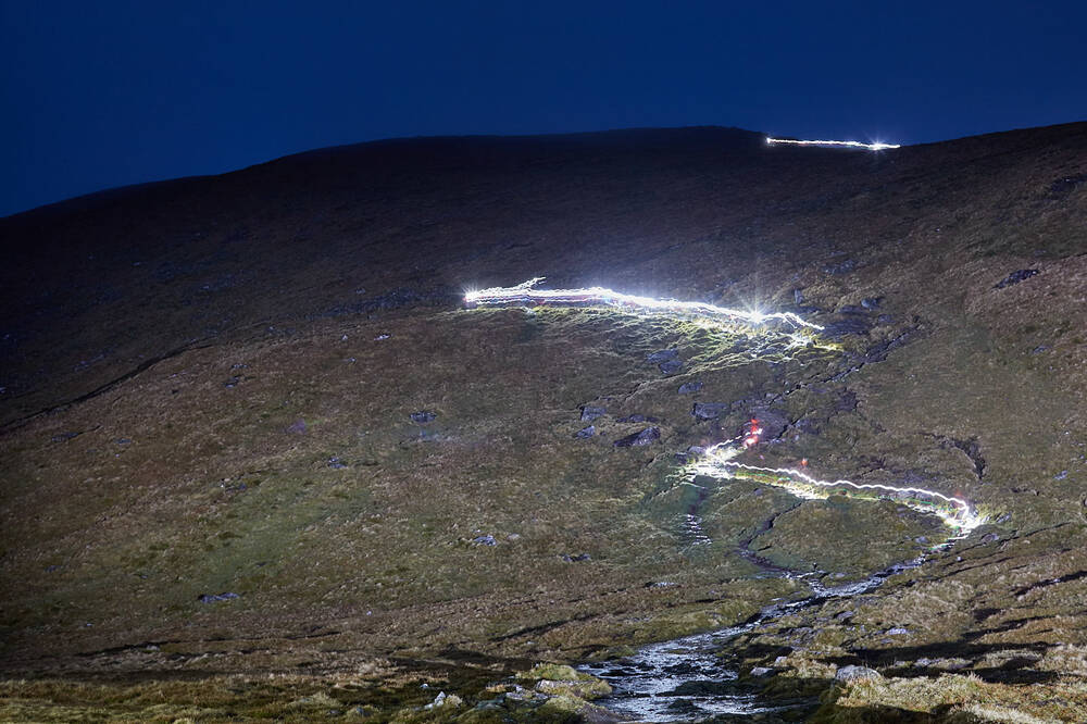 Torchlight can be seen from the mountainside as climbers make their ascent to the summit