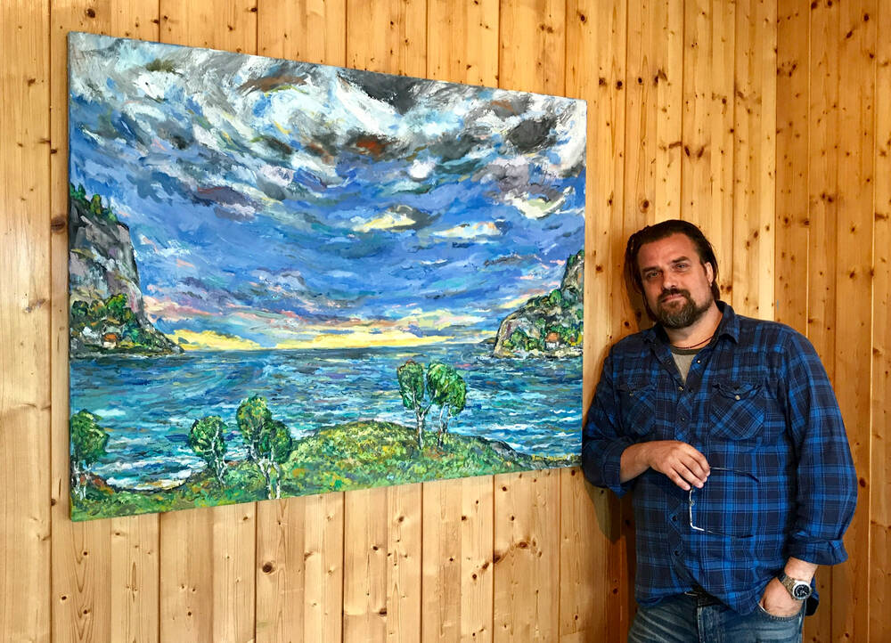 Artist David Sandum stands beside a bold-coloured painting of a Scottish coastline, displayed on a timber wall.