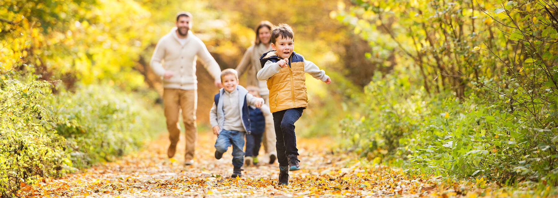 A family running through a woodland in autumn