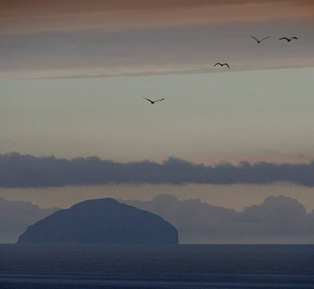 A hazy view of the rounded lump of Ailsa Craig, an island surrounded by calm waters. It is almost silhouetted against lines of cloud in an orangey sky.