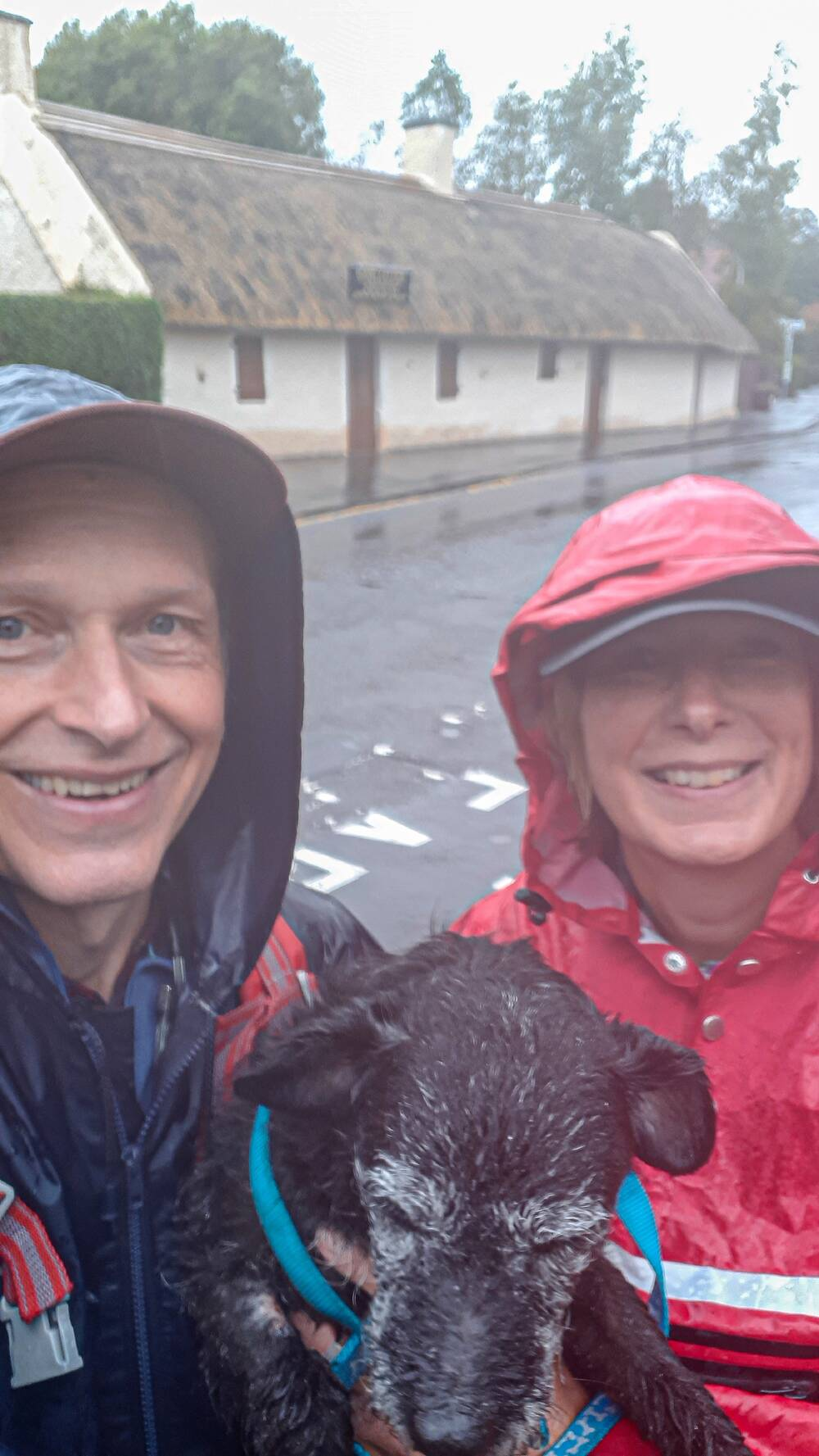 A close-up selfie of a man and a woman in cagoules, standing in front of a thatched cottage in the rain. They hold a very soggy dog between them.