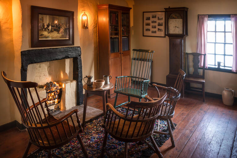The interior of Bachelors' Club, including a fireplace, four chairs and a grandfather clock