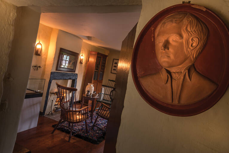The interior of Bachelors' Club, with a portrait of Robert Burns. Through the doorway is a fireplace and four chairs
