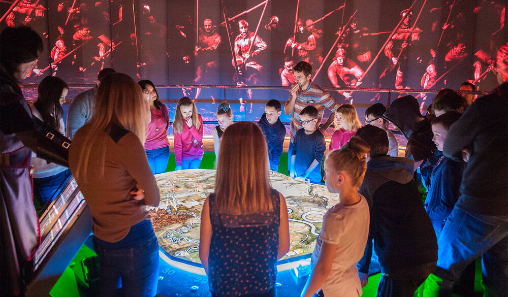 A group of adults and children stand around the illuminated interactive battle table at Bannockburn.