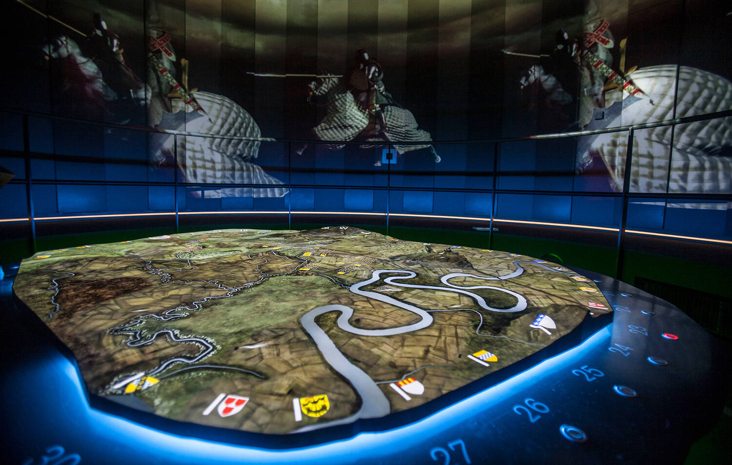 The 3D battlefield lit up in a dark Battle Room. The walls show screens with images of soldiers on horseback, carrying spears.