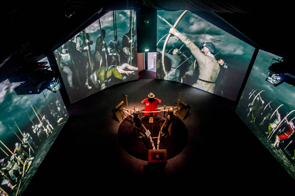 270-degree screens showing scenes from the battle surround a display of weapons and armour in the Battle of Bannockburn visitor centre.