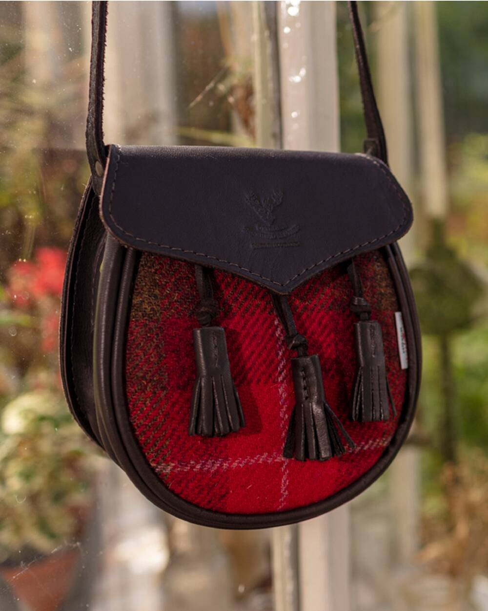 A leather sporran handbag hangs from a handle. It has a red tweed middle with leather tassels.