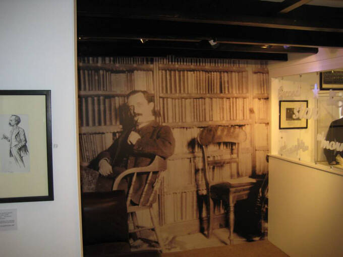 A large photograph of J M Barrie among artefacts in an exhibition room at J M Barrie's Birthplace