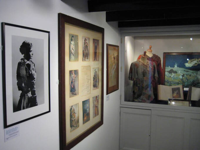 Costumes, prints and artefacts on display in an exhibition room in J M Barrie's Birthplace