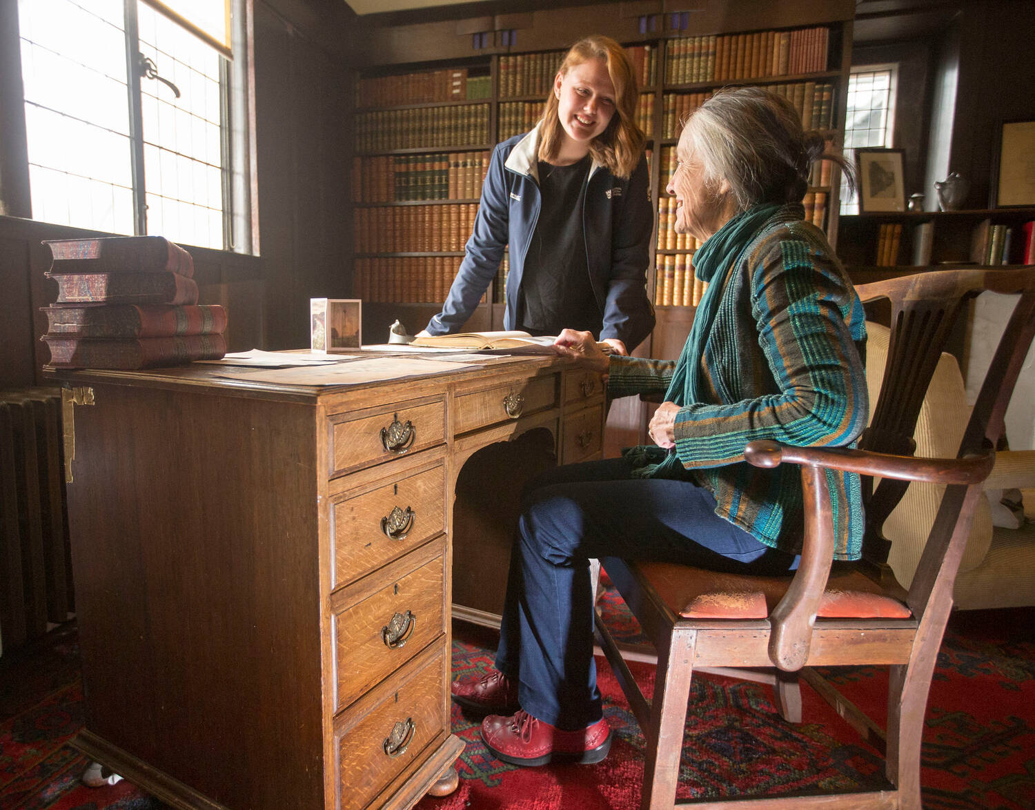 A lady sits at a wooden desk in a study, with a member of National Trust for Scotland staff standing beside her.