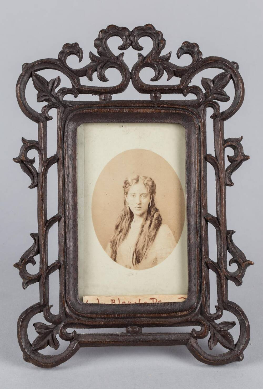 A sepia-coloured photograph of a woman with long hair in a half-up do, wearing a white dress, is displayed in an ornate wooden photo frame.
