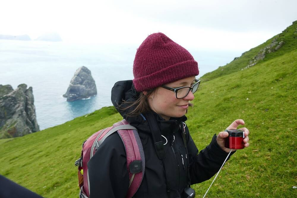 A lady stands on a cliffside on St Kilda holding a sound recorder. She has her eyes closed as if listening carefully.