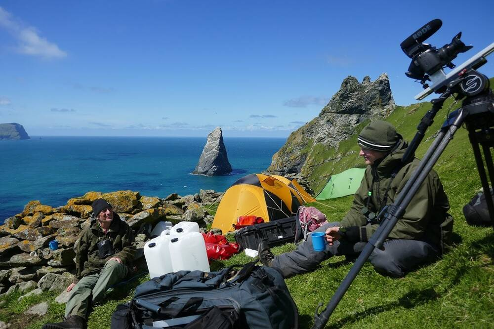 Two men sit in a campsite, on the steep cliffs of Boreray. A yellow tent is pitched in the background and a large camera on a tripod stands in the foreground.