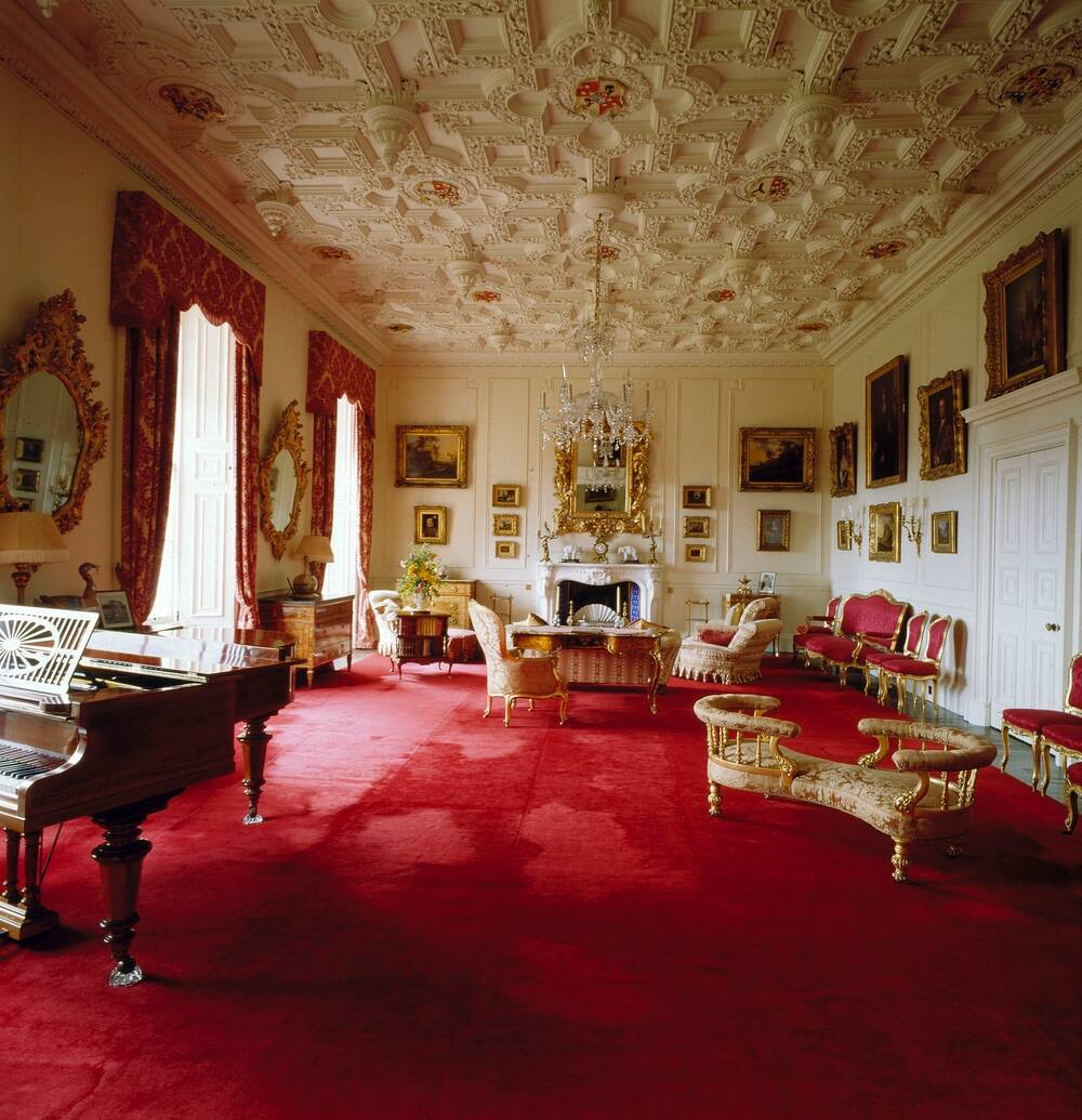 A view of a grand drawing room in Brodick Castle. It has a rich red carpet running the full length of the room. The plaster ceiling is intricately carved in panels with heraldic devices. A piano stands in the foreground, and further back are several sofas and chaise longues. The large windows are draped with long red curtains.