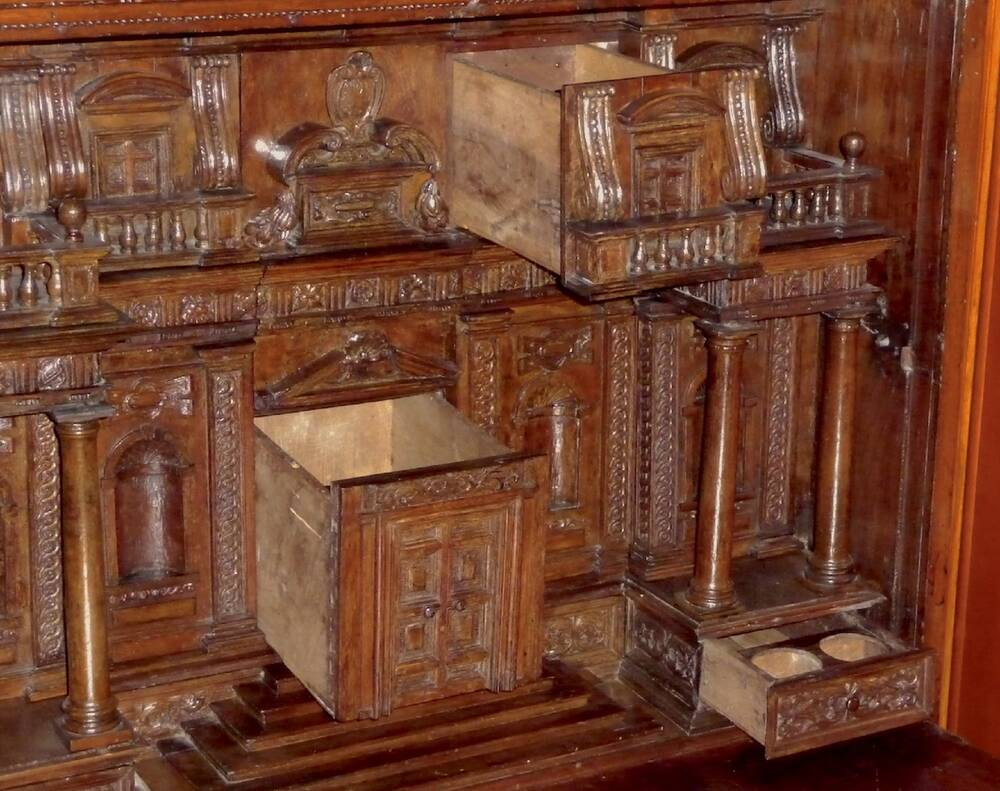 A close-up view of a wooden cabinet, opened up to reveal a collection of different shaped drawers. When closed, the drawers form the shape of a grand house with carved pillars. Two deep drawers in the middle are pulled open, as well as a small drawer on the bottom right, with two inkwell holes inside.