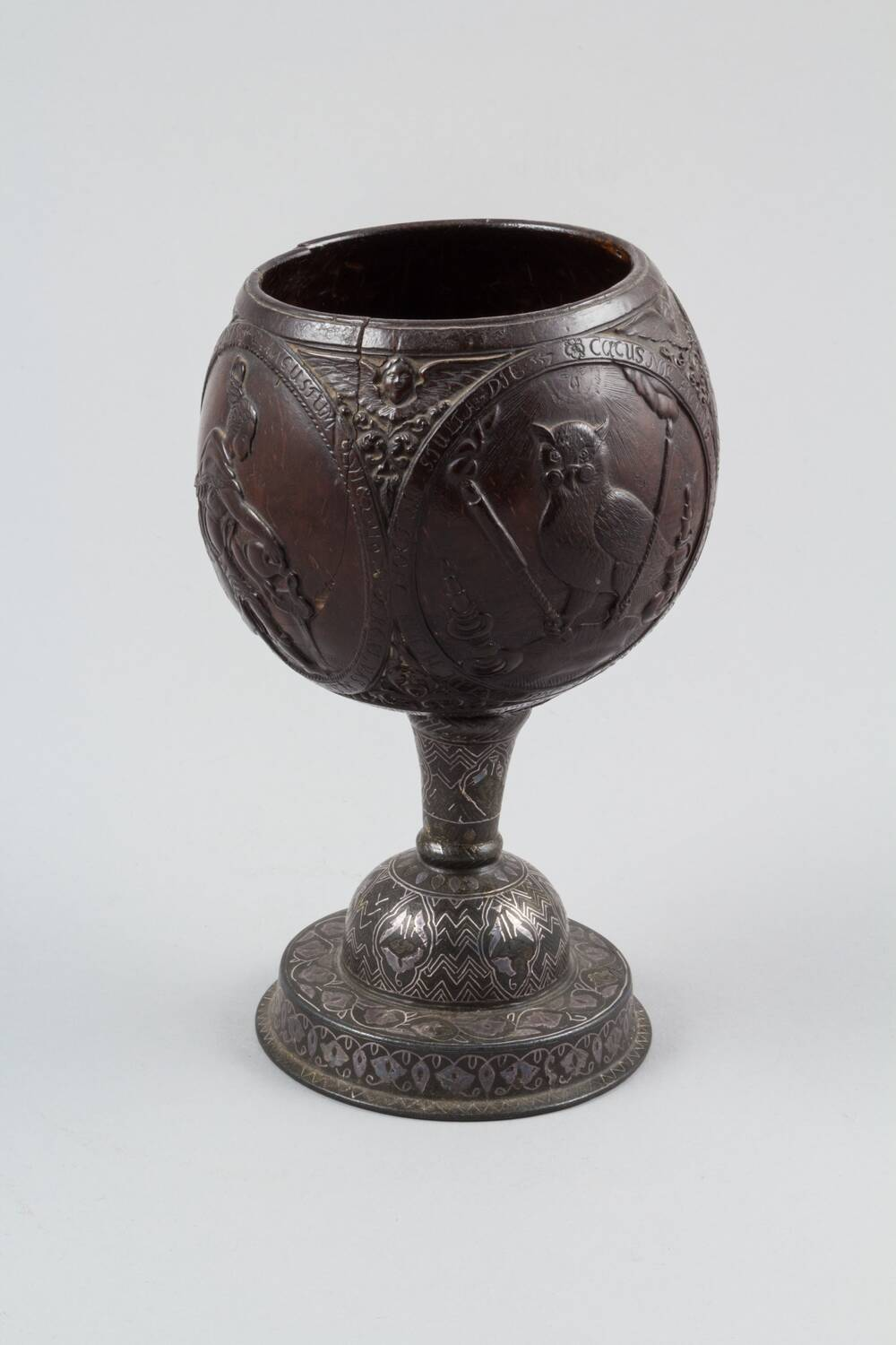 A dark, wooden goblet is displayed against a plain grey background. The top is carved from a coconut shell and has a number of etched illustrations upon it, including an owl. The stem and base have white patterns carved onto them.