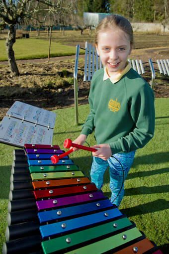 Schoolgirl playing a colourful xylophone in Brodie's garden
