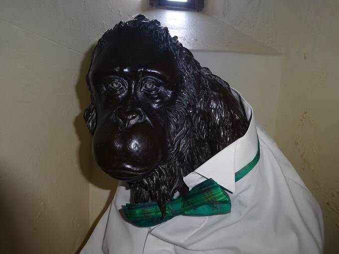 A bronze statue of an orangutan, dressed in a white shirt with a green tartan bowtie.