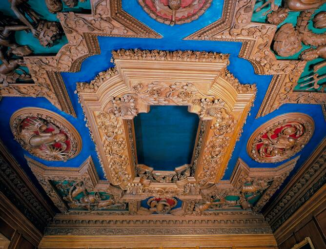 A colour photograph of an ornate and elaborate decorated plaster ceiling. Wooden carvings of creatures and fruits adorn a blue plaster background.