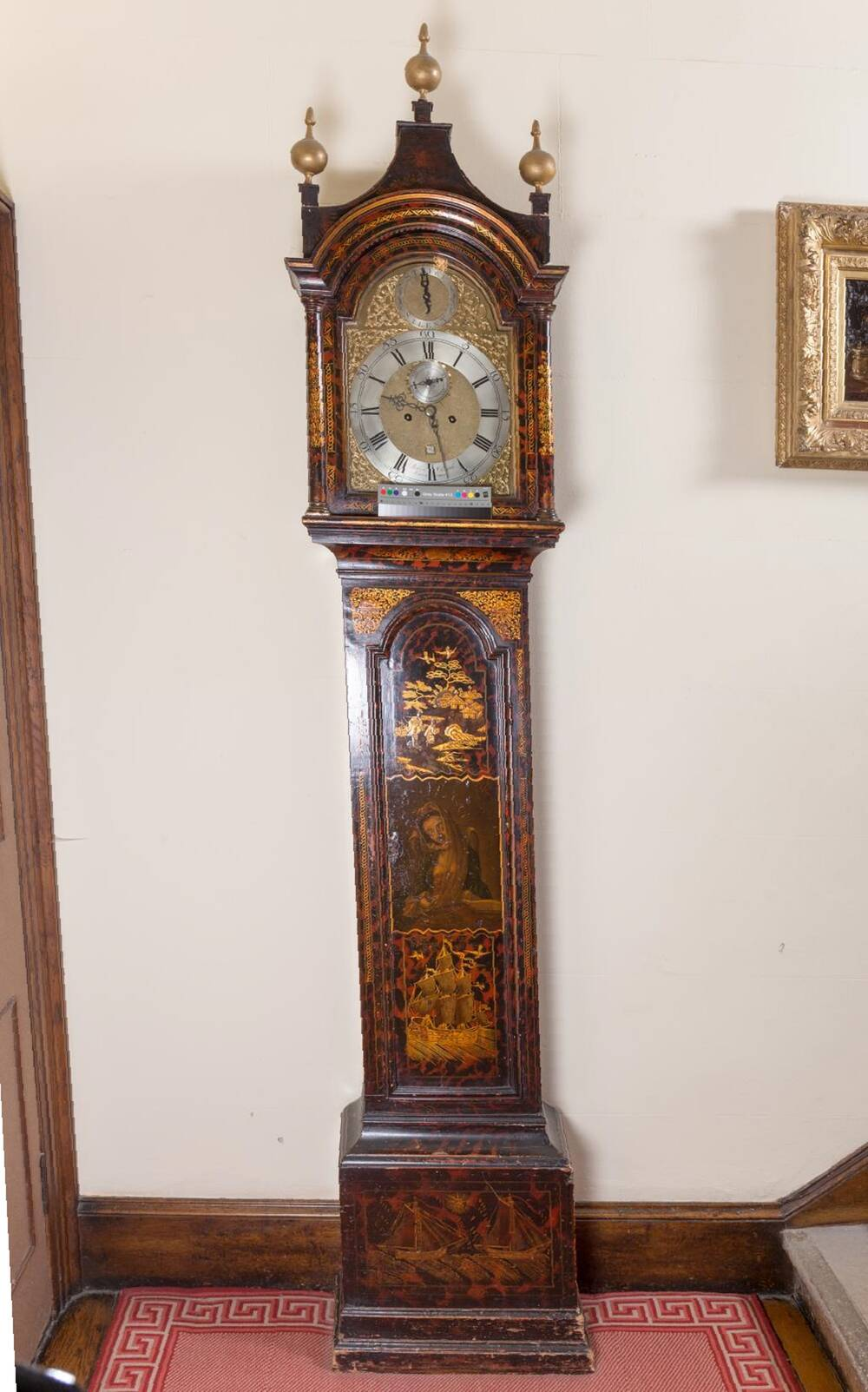 A longcase clock stands against a plain grey wall at the foot of some stairs. It stands on a red and white patterned rug. Its wooden case is highly polished and decorated with patterns and an image of a ship and a saintly woman. There are elaborate bronze finials on top of the clock.