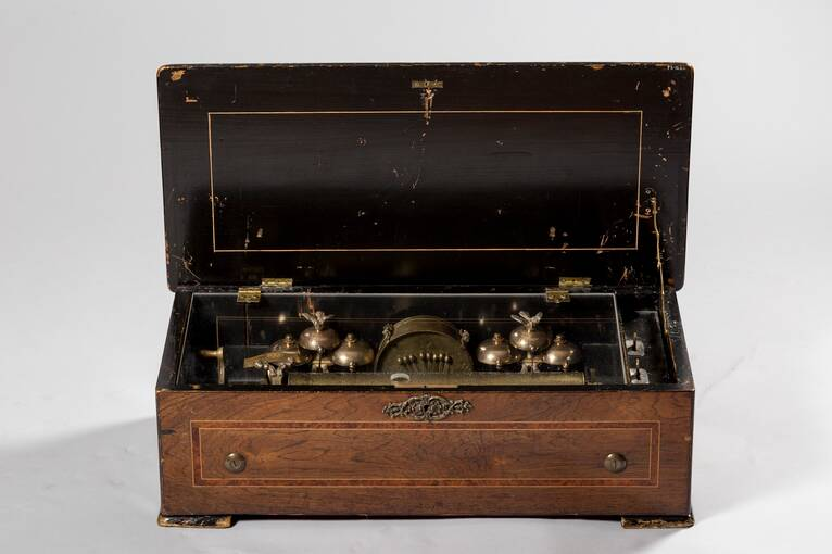 An old-fashioned wooden musical box, with the lid open to reveal the mechanisms inside.