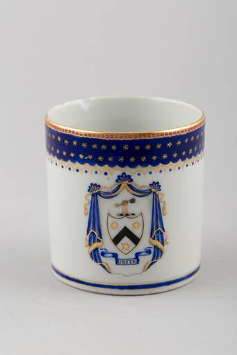 A china cup from a dinner service. It has a blue rim with gold edging. On the main part of the cup it has a shield surrounded by blue drapes and the motto Unite in a scroll underneath.