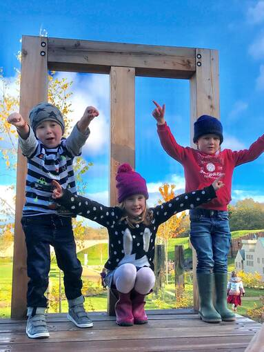 Three children stand or crouch on a giant wooden kitchen chair. The sky is bright blue in the background.
