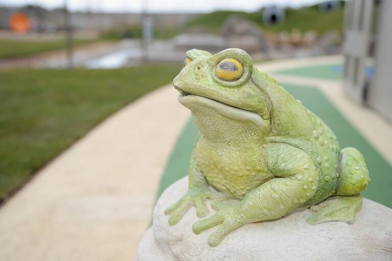 A model of a green toad sitting on a rock in a garden.