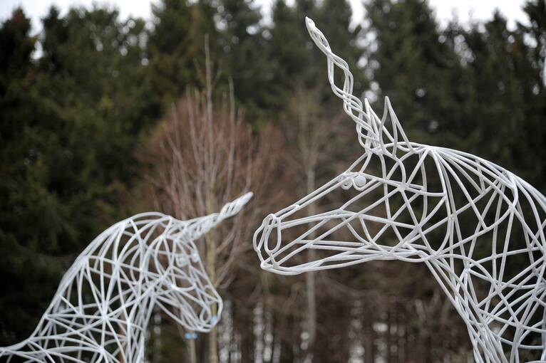 Two white woven unicorn statues stand outside, with woodland in the background.