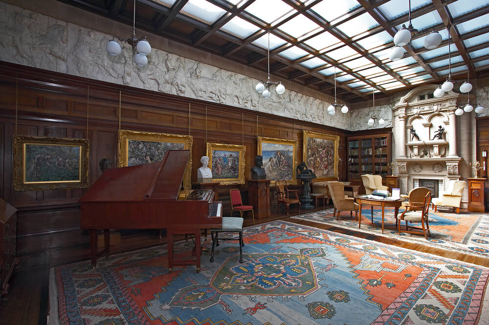 A long wood-panelled room with many framed oil paintings on the walls. A piano stands to the side with its lid open. A plaster frieze runs along the top of the wall. The ceiling is lit by glass square window panels.