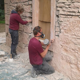 Two stonemasons work on a building beside a boarded-up window. The man kneeling in the foreground wears a mask and holds a large tool.
