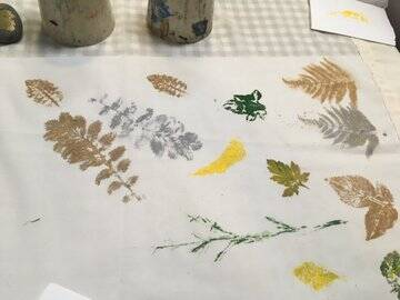 A gauze panel,printed with leaves, grasses and feathers, lies on a checked tablecloth.