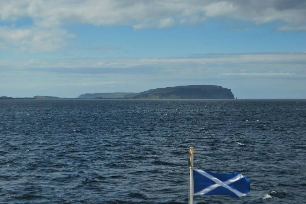 A view of Canna from a boat, with a saltire flag flying from the prow.