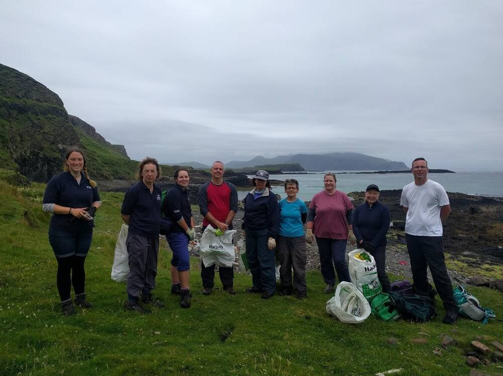 Group photo of the Conservation Volunteers on the Isle of Canna with the sea in the background.