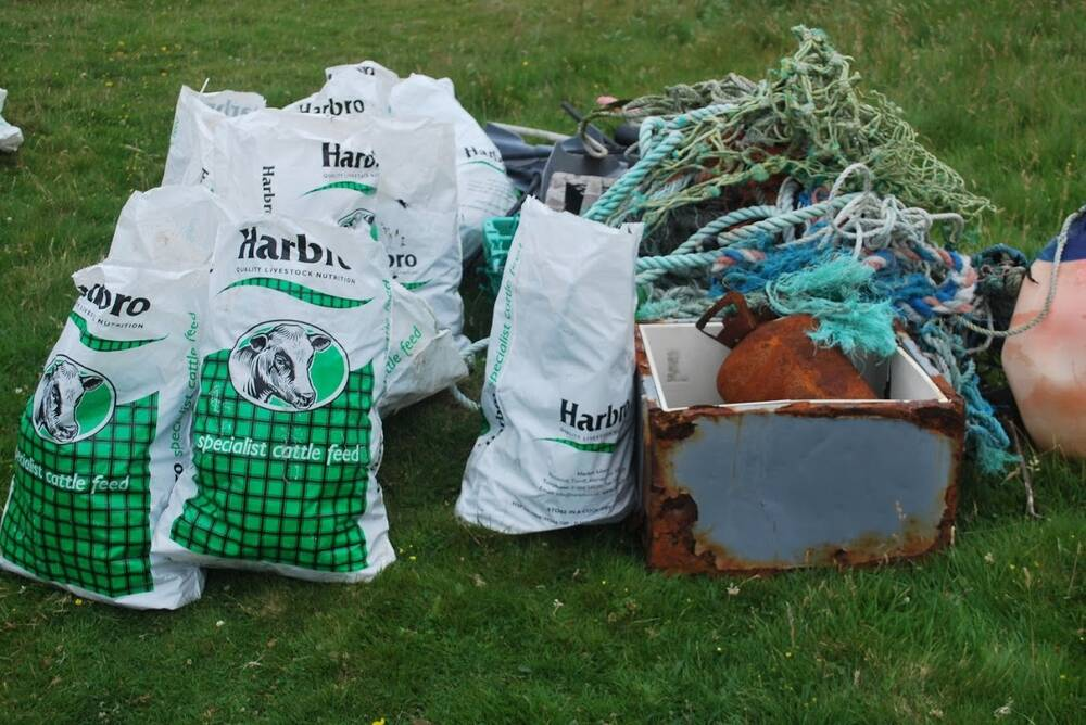 Bags filled with plastic waste and rope lie on the grass.
