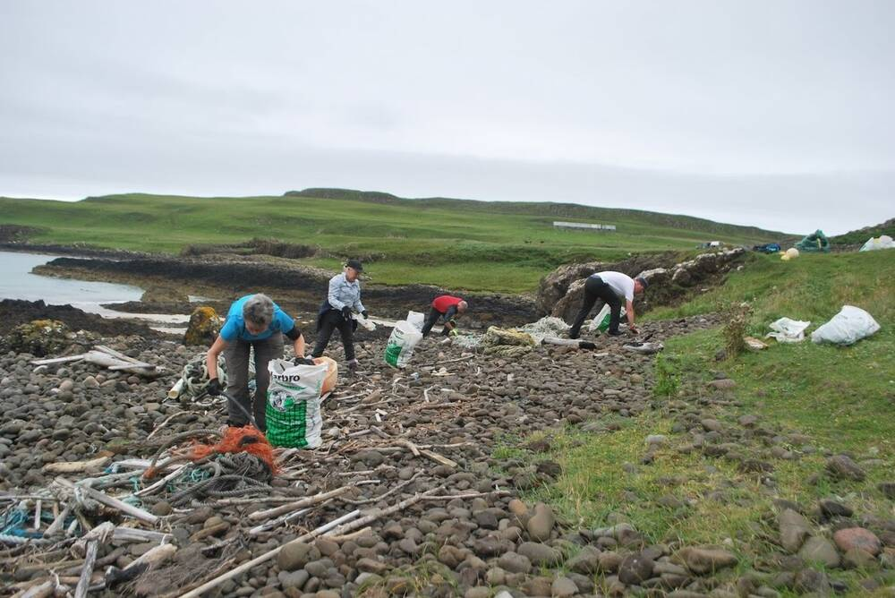 Conservation volunteers picking up rubbish along the coast of Canna.