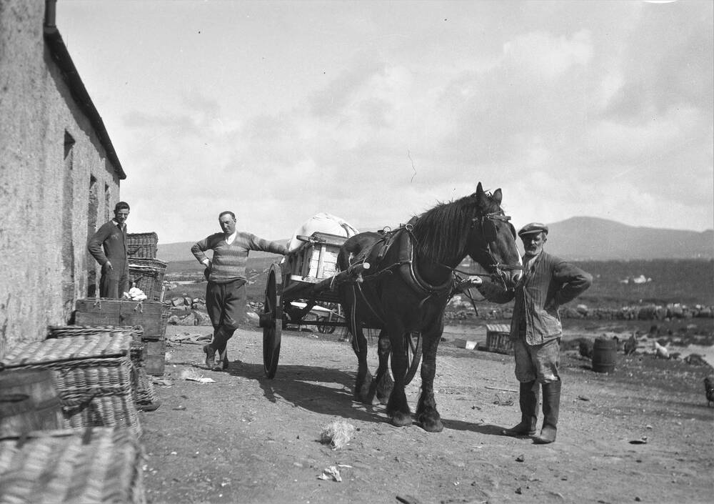 A black and white photo of three men standing with a horse and cart outside a stone building. Baskets and crates are piled up beside the wall.