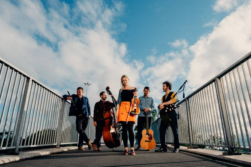 Five band members stand on a bridge holding their instruments: a flute, double bass, violin, guitar and bagpipes.