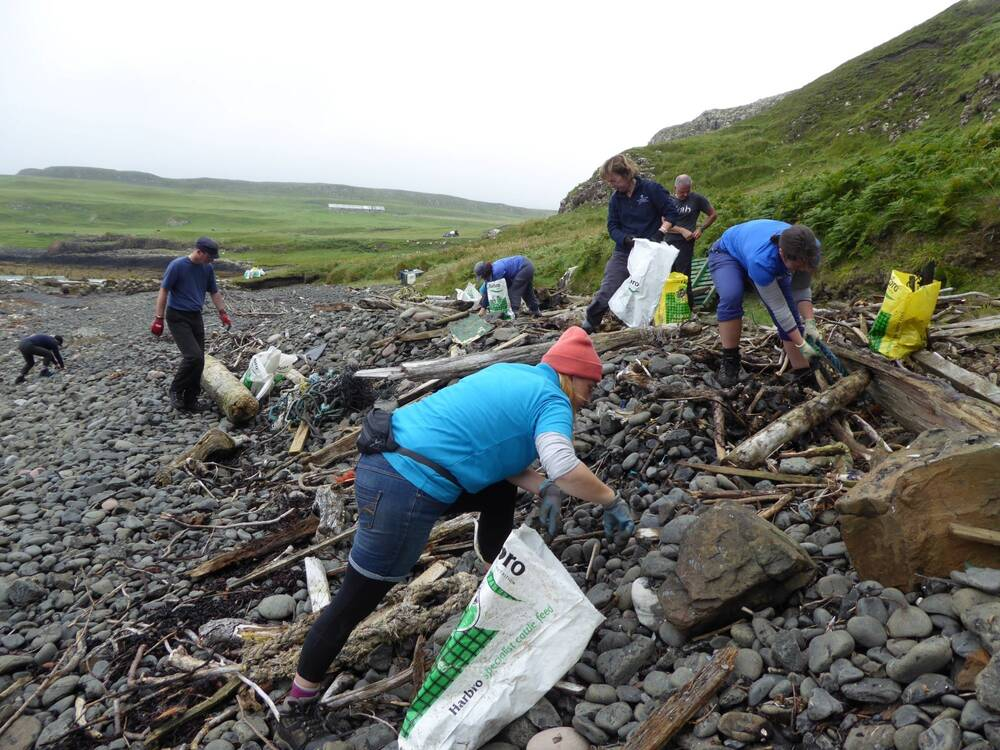 A group of people sort through rubbish on a stony beach, mostly at the high tide mark.