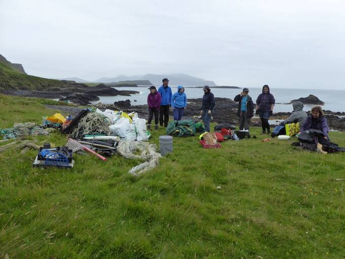 A group of people stand in a field beside the shore on Canna. They have collected a huge pile of rubbish, including rope and plastic pallets.