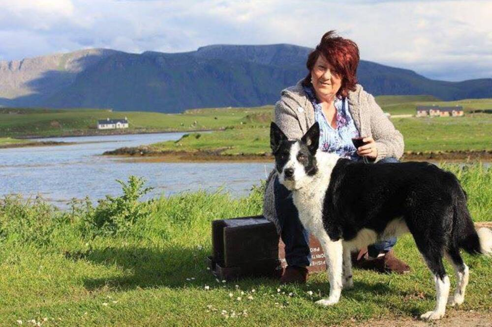 A woman sits on a low bench, with her black and white collie standing in front of her. Canna Bay can be seen behind her, and mountains in the distance.